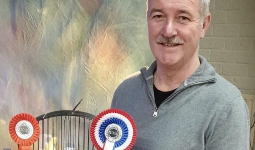 Wim Reedijk met zijn kanarie, de algemeen kampioen.