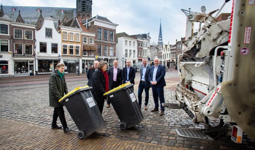 Inge Boot, directeur Cyclus en wethouder Hilde Niezen rollen de eerste containers naar de vuilnisauto. Foto: PR