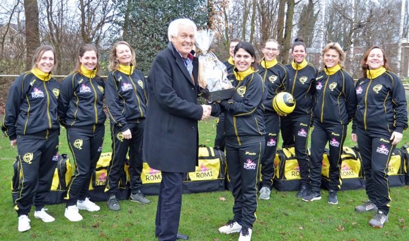 Financieel directeur Roel van de Meent van Kinderopvang ROMI ontvangt als dank voor de sporttassen bloemen van VSCO'61 Vrouwen 30+.