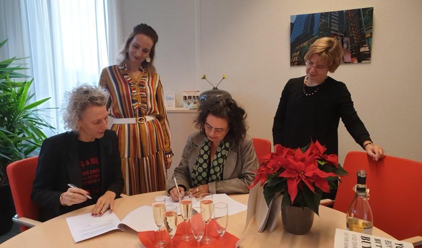 Ondertekening samenwerkingsovereenkomst door Sabien Raams en Eta Mulder van Dimence en Sylvia van Drenth en Evelyn Wannet van Twomorrow.