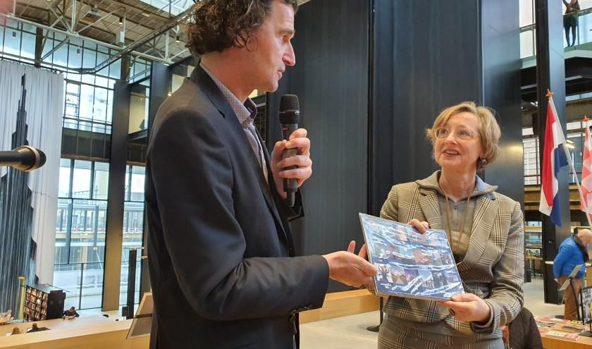 Tim van der Avoird geeft het eerste exemplaar van het nieuw plengske aan Petra Robben van het Stadsmuseum.