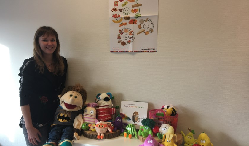 Dominique Flink met verschillende poppen en knuffels in haar praktijk.