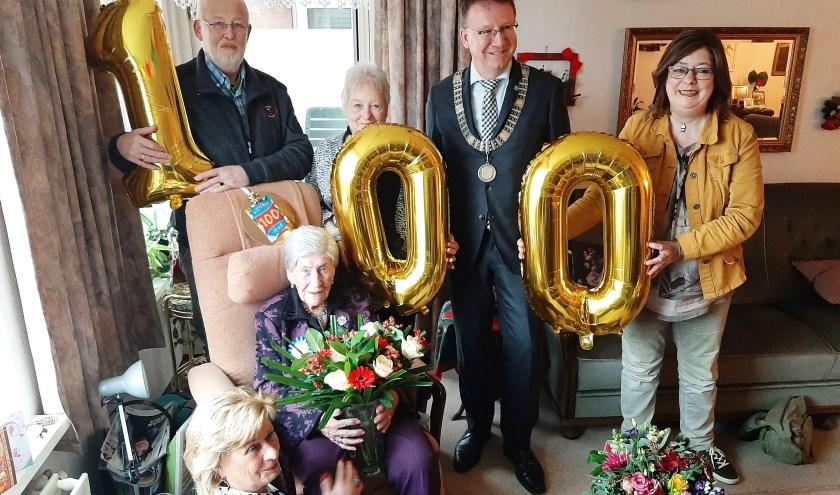 De honderdjarige Alida van Soolingen-van der Graaf - met bloemen - als stralend middelpunt omringd door burgemeester Patrick van Domburg en enkele familieleden. (Foto: Rinus Verweij)