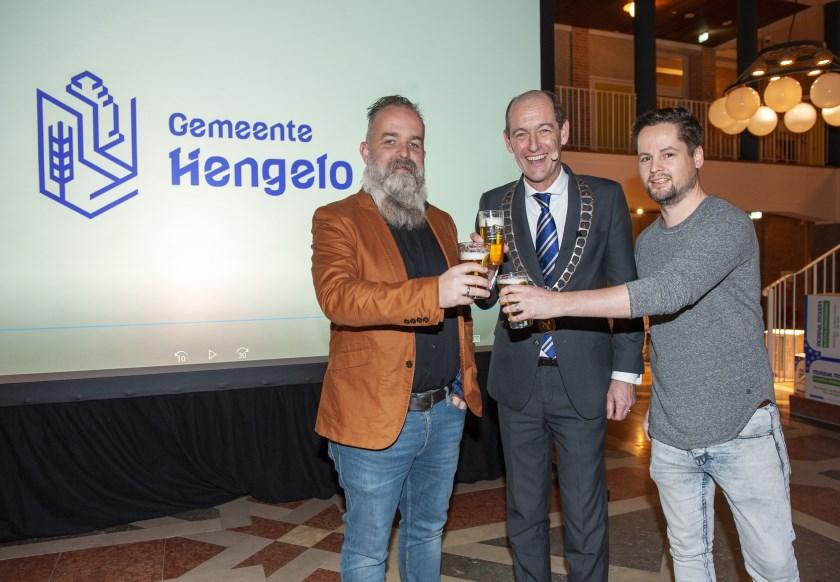 Tom Schepers (l.) en Daniël Bol (r.) van Creative Bastards toosten met burgemeester Sander Schelberg op het nieuwe logo.