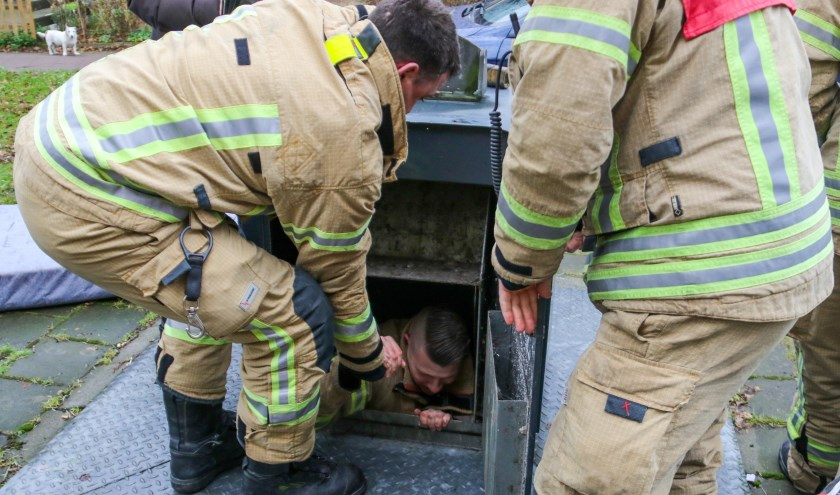 Brandweerman kruipt in afvalcontainer om portemonnee eruit te vissen.