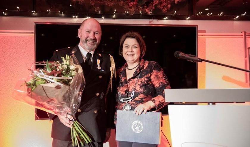 Vrijwillige brandweerman Henri van Beek samen met de burgemeester. Foto: Edwin Bolt