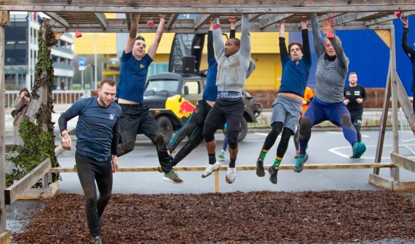 Deelnemers aan de Hammerrun in actie op een van de twintig hindernissen.