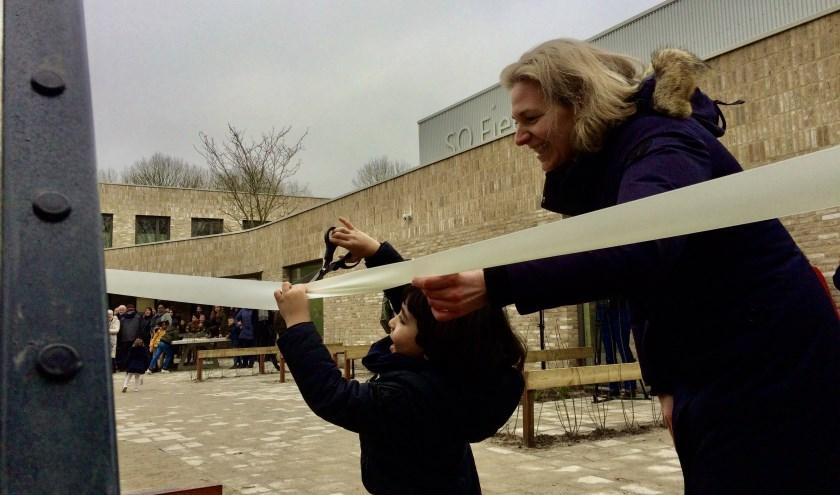 Youssef (4) knipt het lint door om het kunstwerk op het schoolplein, geassisteerd door wethouder Anke Klein. Foto: PR
