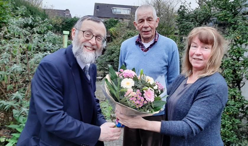 Rabbijn Shmuel Katz overhandigt een bloemetje aan Wilke Middelhoven. In het midden Jaap Krocké die samen met Bram Geurtsen de coördinerende taken nu op zich neemt. (Foto: Martin Brink/DPG Media),