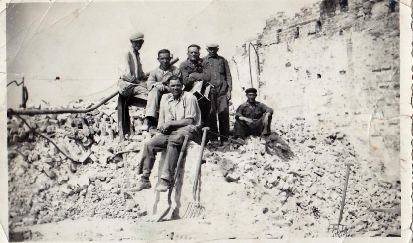 Joops schoonvader Jan Roos (midden zittend) samen met andere vrijwillige puinruimers poserend op de resten van de gebombardeerde stad. Foto: Joop van der Hor