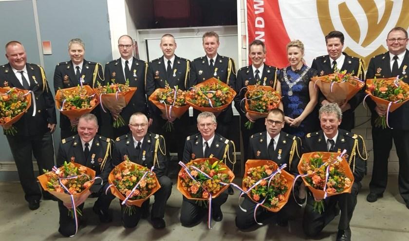 De gedecoreerde vrijwilligers van de brandweer met burgemeester Jacqueline Koops.