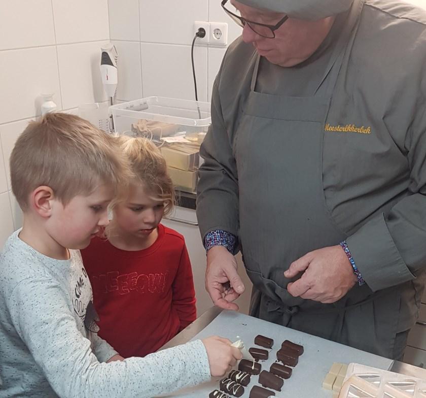 Onder toeziend oog van Huub versieren de kinderen de bonbons tot ware kunstwerken.