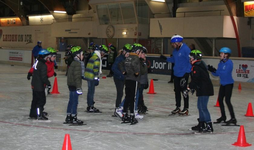 In groepjes kregen de kinderen les op de binnen- en buitenbaan van de schaatshal.