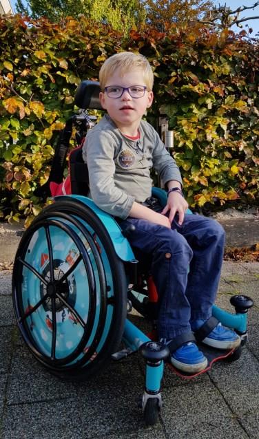 Tim in zijn rolstoel. Binnenkort krijgt hij een grotere rolstoel en die past niet meer in de auto van zijn ouders