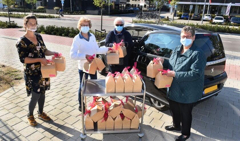 <p>Mari&euml;lle de Vries en Corine Derksen van de Stadskamer reiken de pakketjes uit aan Lucy Siebes en Kitty Bulsink (foto Roel Kleinpenning)</p>