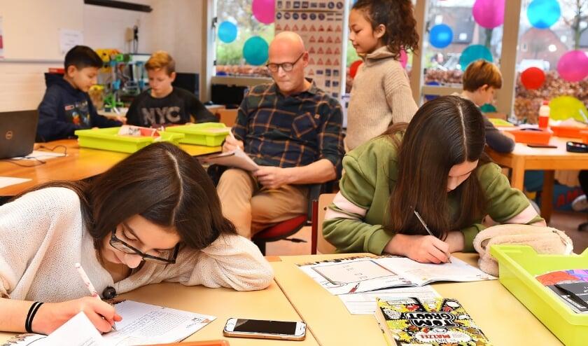 Jante Luimes, docent unit 3 tienercollege basisschool 't Prisma locatie de Huet in overleg met een leerling. (foto: Roel Kleinpenning)
