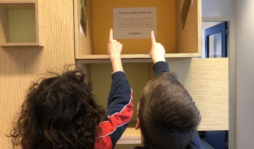 Leerlingen bewonderen eigen werk tijdens foto-expositie.