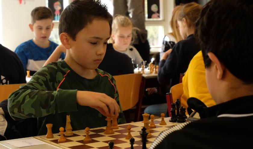 De kinderen speelden in teams van vier, ieder met een schaakbord, tegen een team van een andere school.