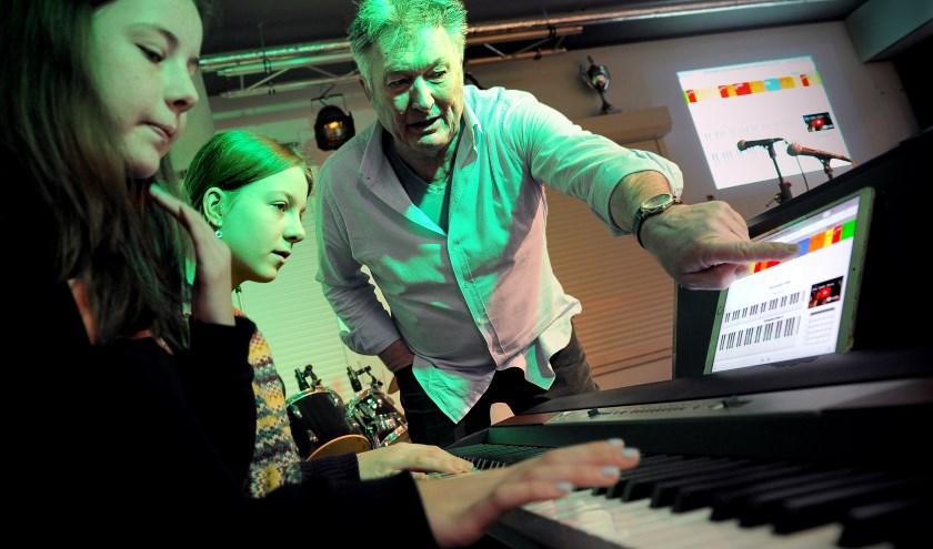 Docent popmuziek Philibert van den Bosch geeft leerlingen van het Beekdal Lyceum uitleg bij de app Qords.