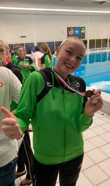 Marit toont trots haar bronzen medaille.