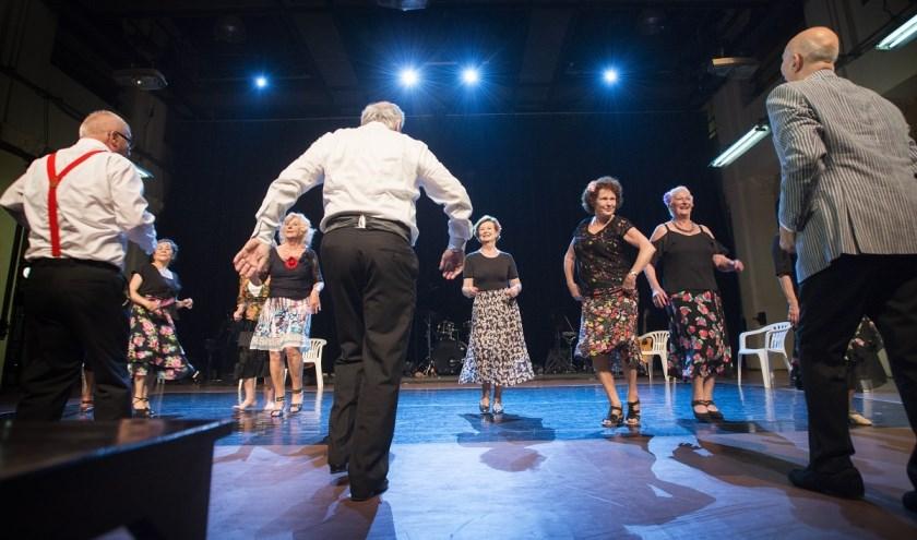 Een aantal senioren danst salsa tijdens participatieproject Dans in school (educatieve dienst van het Internationaal Danstheater).