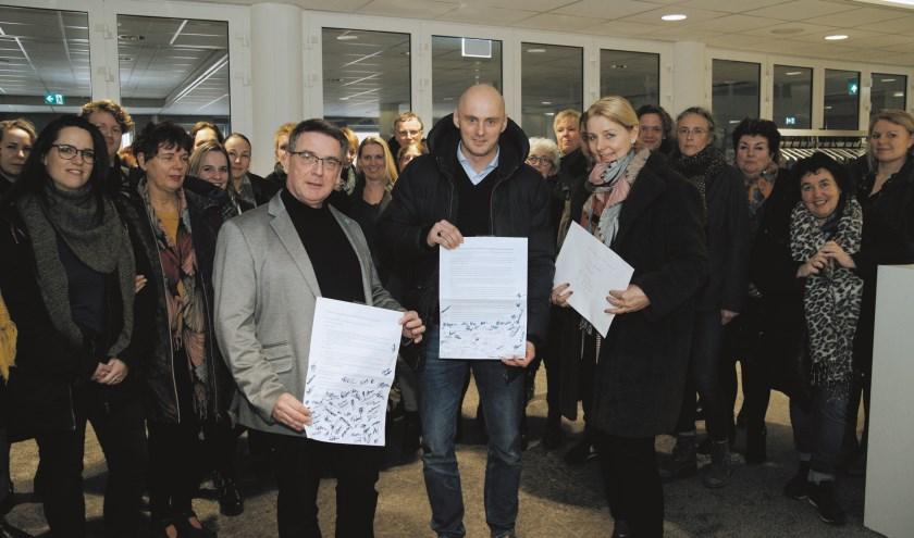 Rob Raayman (l) heeft uit handen van Stefan de Jonge de petitie in ontvangst genomen. Rechts Monique Kampman van IKC Het Startblok.