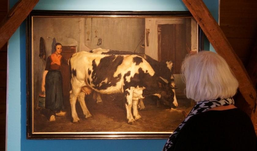 Een bezoeker bekijkt 'Boerin met koeien in een stal'. (foto: Voerman Museum Hattem)
