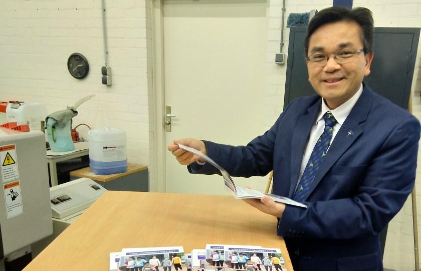 Pastoor Thanh Ta bekijkt met trots het eerste exemplaar.