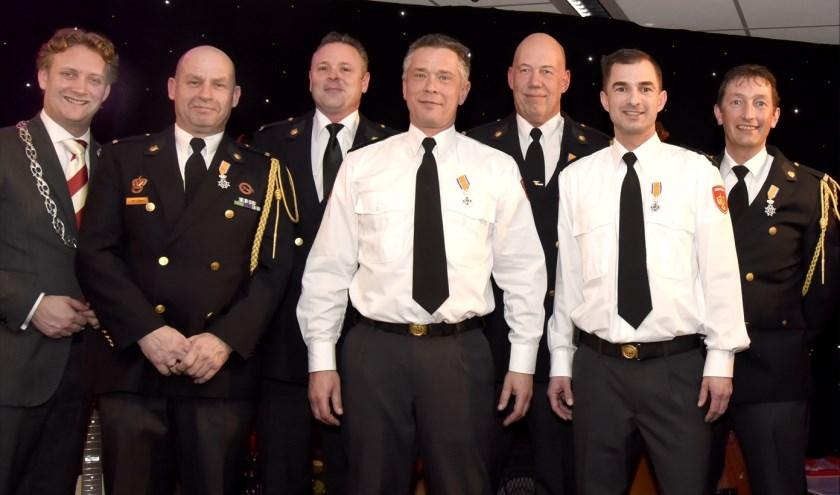 Burgemeester Pieter Verhoeve met de zes gedecoreerde brandweerlieden. Foto: Marianka Peters