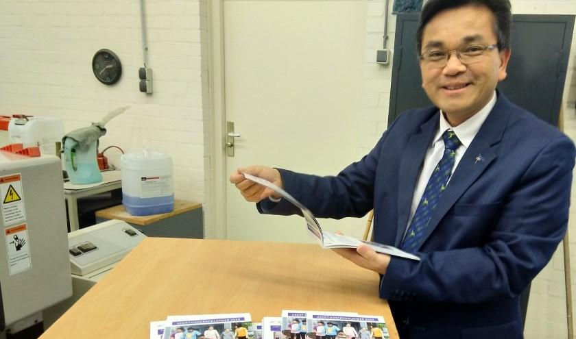 Pastoor Thanh Ta bekijkt met trots het eerste exemplaar van de gratis veertigdagenkalender. (foto: Parochie Sint Willibrordus)