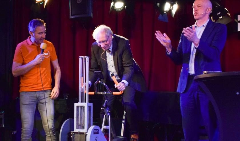 Presentatoren Marc Pruijn (rechts) en Frans Post (midden) testen de recyclefiets van Rolph Adriaansen (links), tijdens het Milieucafé in Paradox