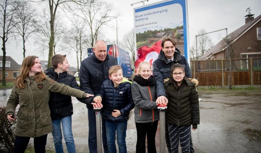 Gedeputeerde Boerman (links) en wethouder te Rietstap van Hardenberg onthullen samen met kinderen uit Balkbrug het bouwbord.