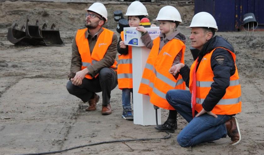 Wethouder Kraijo, Liam, Lieke en meester Marcel kijken hoe de eerste paal voor ikc De Twijn in de grond wordt geboord.