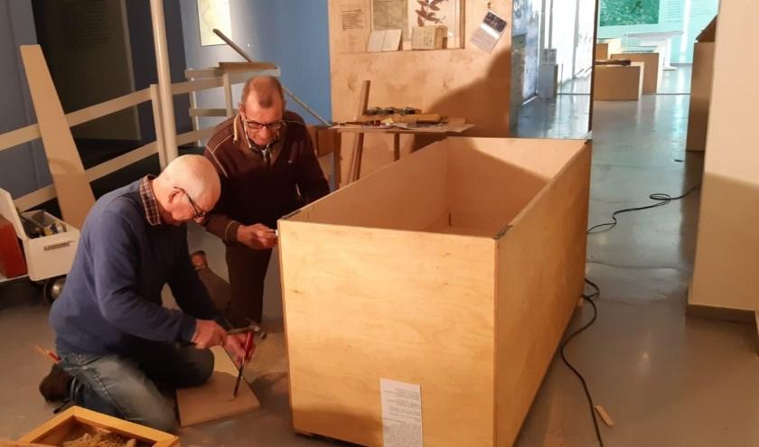 Medewerkers Theo Godschalk en Frans Stevens zijn druk bezig met de verhuizing van het Liemers Museum naar HAL12. (foto: PR)