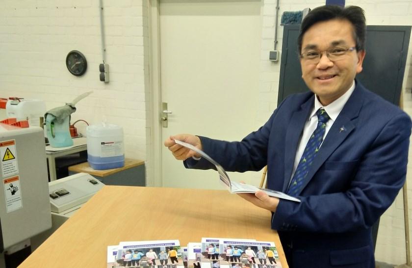 Pastoor Thanh Ta bekijkt met trots het eerste exemplaar
