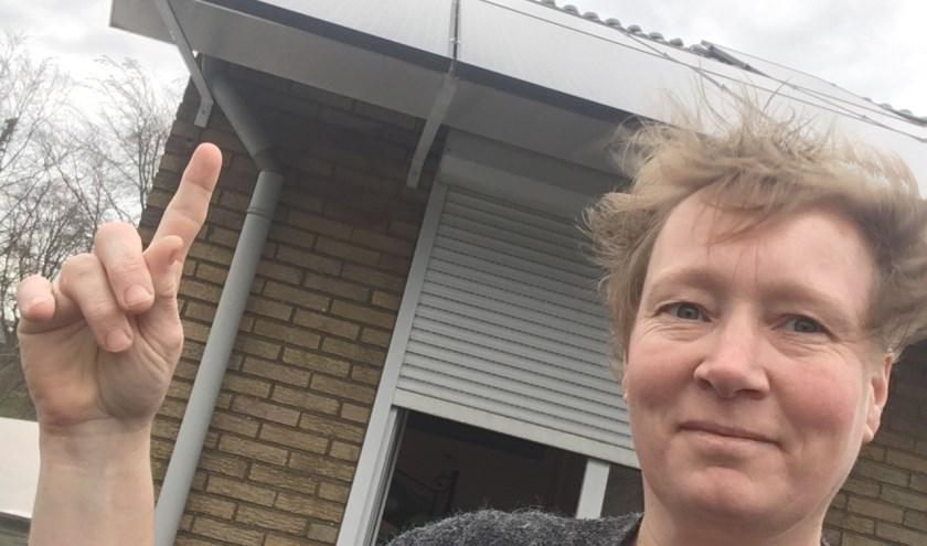 Emely Meijerink wijst naar de zonnepanelen op het dak van haar huis. (Foto: NEW)