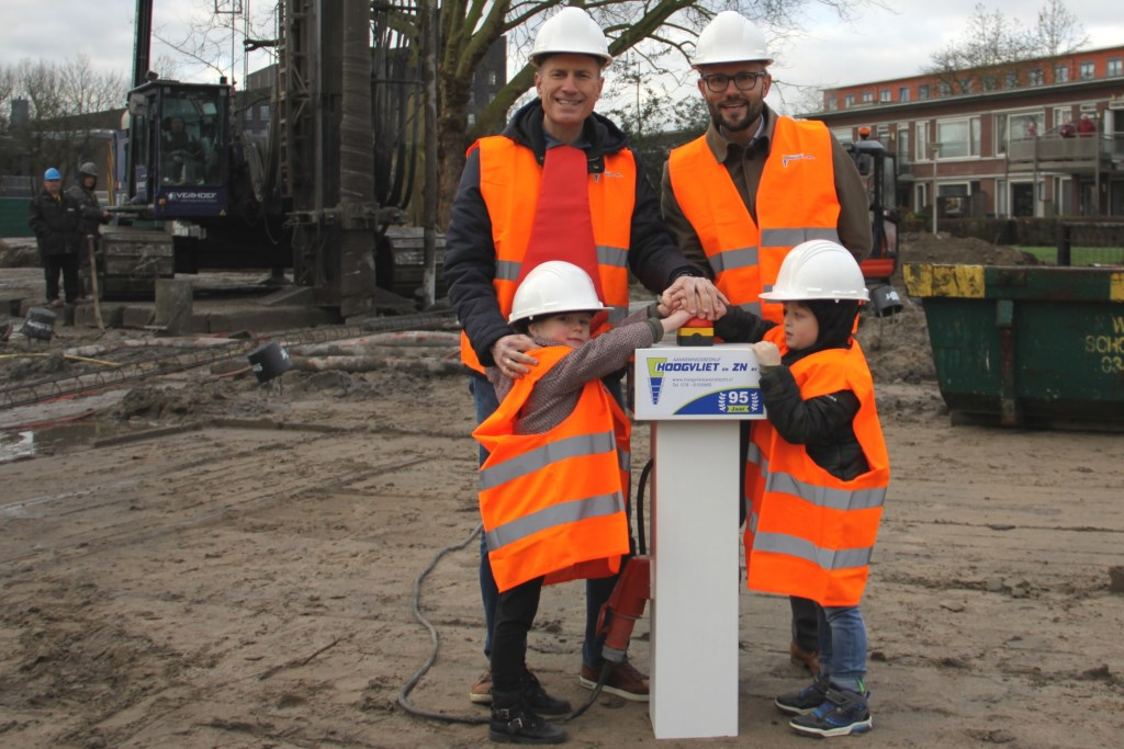 Wethouder Kraijo, Lieke, Liam en meester Marcel drukken op de rode knop en zetten zo de machine in werking voor de eerste paal van ikc De Twijn.  © DPG Media