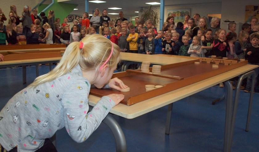 Opperste concentratie bij Kiruna (bijna 7) tijdens de spannende finale van de sjoelcompetitie op basisschool De Akker.