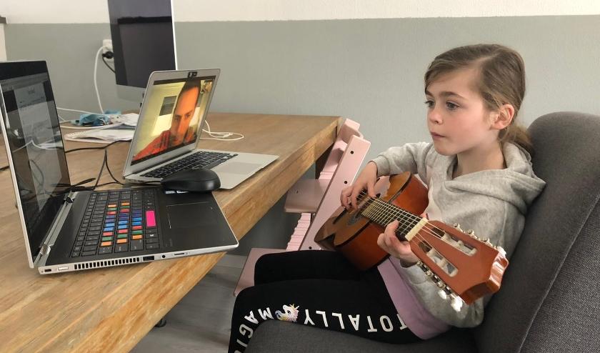 Faye krijgt gitaarles op afstand.