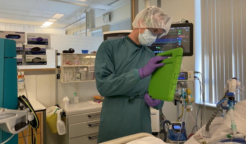 Een IC-verpleegkundige laat via beeldbellen aan familie zien hoe de patiënt in bed ligt.