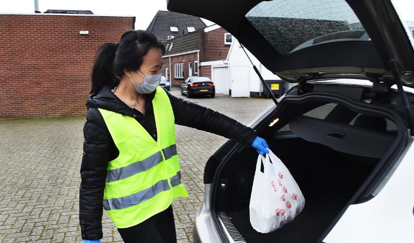 Lin van Golden Dynasty legt het bestelde eten in de auto van Arnold Woerts uit Zelhem. (foto: Roel Kleinpenning)