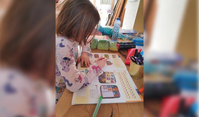 Deva Baan van zeven maakt haar rekenwerk gewoon in het schrift dat ze op school gebruiken. (foto Marieke Baan)