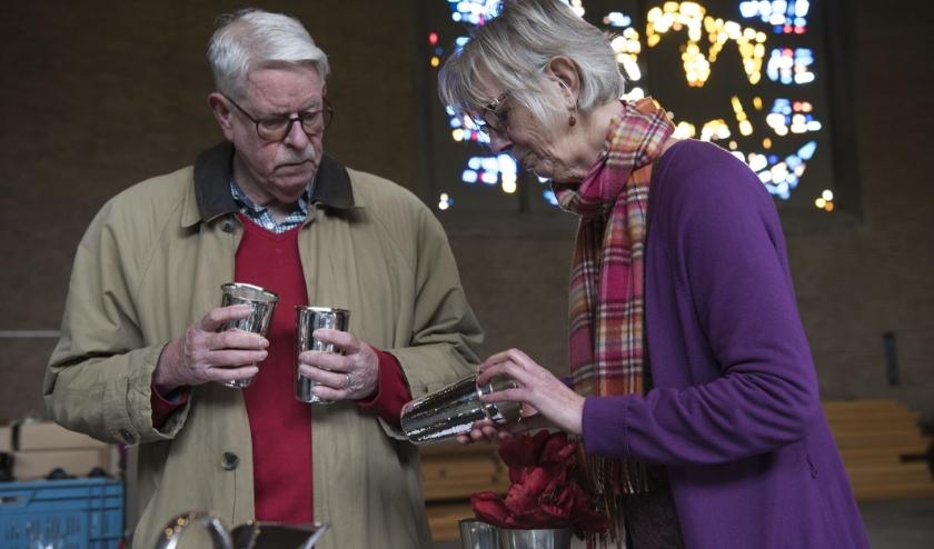 Janneke en Henk hebben belangstelling voor de bekers die de Opstandingskerk in Arnhem op de boedeldag verkoopt.