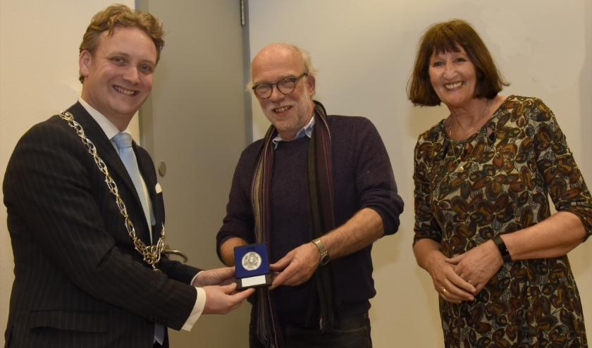 Burgemeester Pieter Verhoeve overhandigt de vrijwilligerspenning aan 'meester' Frans Dubois. Foto: Marianka Peters