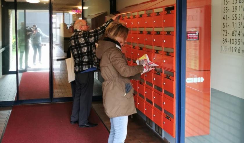 Vrijwilligers bezorgen in Zevenkamp flyers over welke hulp er vanuit Coronahulp Zevenkamp gegeven kan worden.