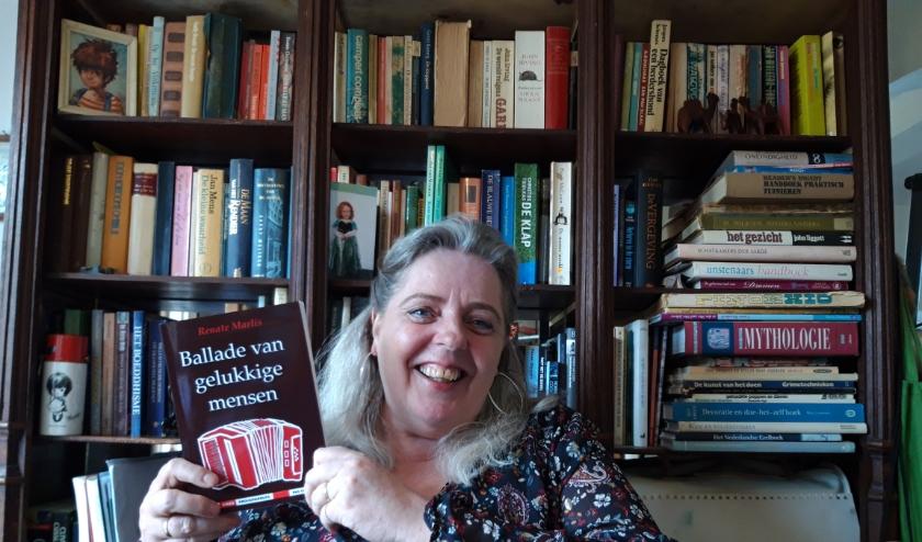 Vol trots toont Renate Maris haar novelle 'De Ballade van Gelukkige Mensen'.  'Mijn opa las mij voor uit sprookjesboeken uit de bibliotheek in Hoogvliet. Hij legde de basis voor mijn schrijven. Foto: Joop van der Hor