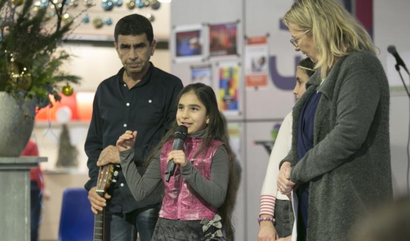 Abdullah uit Landgraaf met zijn dochter Naja geinterviewd door Esther op een Syrie feestavond.(foto Jan ten Haaf)