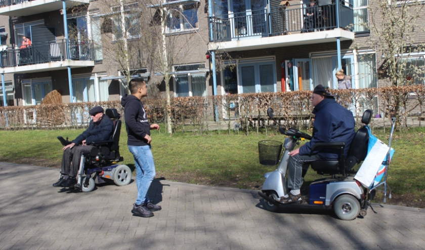 Andrew verwelkomt Henk en Peer, die gezeten in hun rolstoelen met veel enthousiasme de bewegingslessen volgen. (Foto: Henk Jansen)