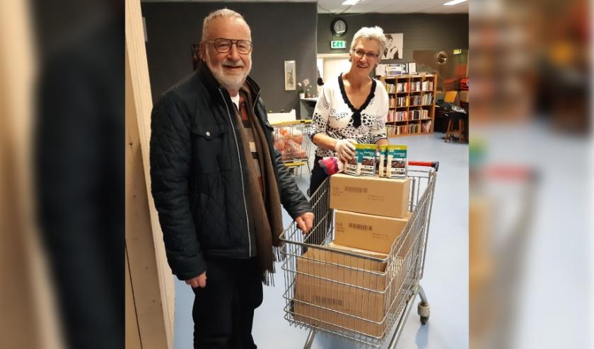 Mia van Rosendaal, bestuurslid van de Voedselbank, neemt de rijst in ontvangst uit handen van Harapan voorzitter Jos van der Heijden.