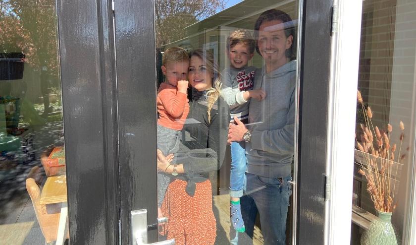 Thomas en Jolien Hagenvoort met Sam en Pepijn achter het weerspiegelende glas in de woonkamer. (Foto: Janske ter Horst)